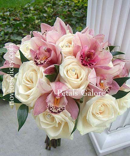 Exquisito bouquet de novia de orquídeas en tonos rosa brillante y hermosas rosas en tonos crema adornado con alfileres de strass