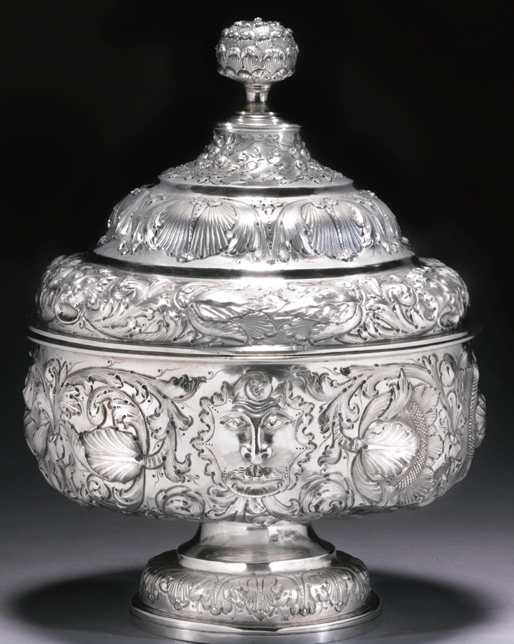 A PORTUGUESE SILVER BOWL AND COVER, MAKERS MARK MF (ALMEIDA NO. L-415) CONJOINED, LISBON,  LATE 17TH CENTURY    the circular bowl on spreading foot boldly embossed and chased with masks, flowers and scrolling foliage, stepped domed cover similarly decorated and incorporating fruit, bud finial