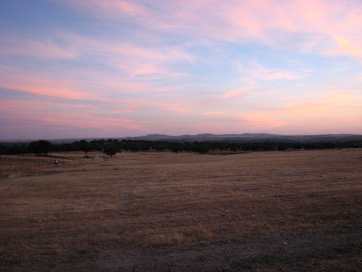 Una vez el sol se ha marchado, la luz ya sólo queda en el cielo pintando las nubes de violetas y ocres. Estamos cerquita de Santa Marta de Magasca y al fondo tenemos la Sierra de Valdefuentes.