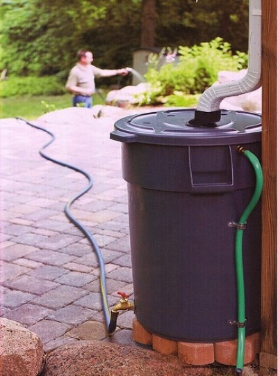 Rain barrel made with a garbage can. The green hose at the right side is for when your barrel gets too full - it will drain off to the side.  I can't wait to get my rain barrel (not that we've had any darned rain)!!