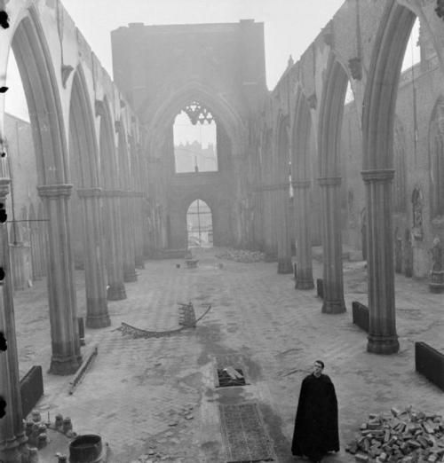 A priest stands in the roofless shell of St. George's Roman Catholic Cathedral, on the corner of St. George's Road and Lambeth Road in Southwark, South East London. The Cathedral was severely damaged by an incendiary bomb attack in 1942.