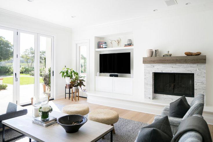 "The television blends in with the decor nicely by being featured in a built-in entertainment center adjacent to an updated fireplace. ""We transformed the original fireplace into a clean, modern fireplace by adding whitewashed brick and a reclaimed mantel,"" says Strickler."