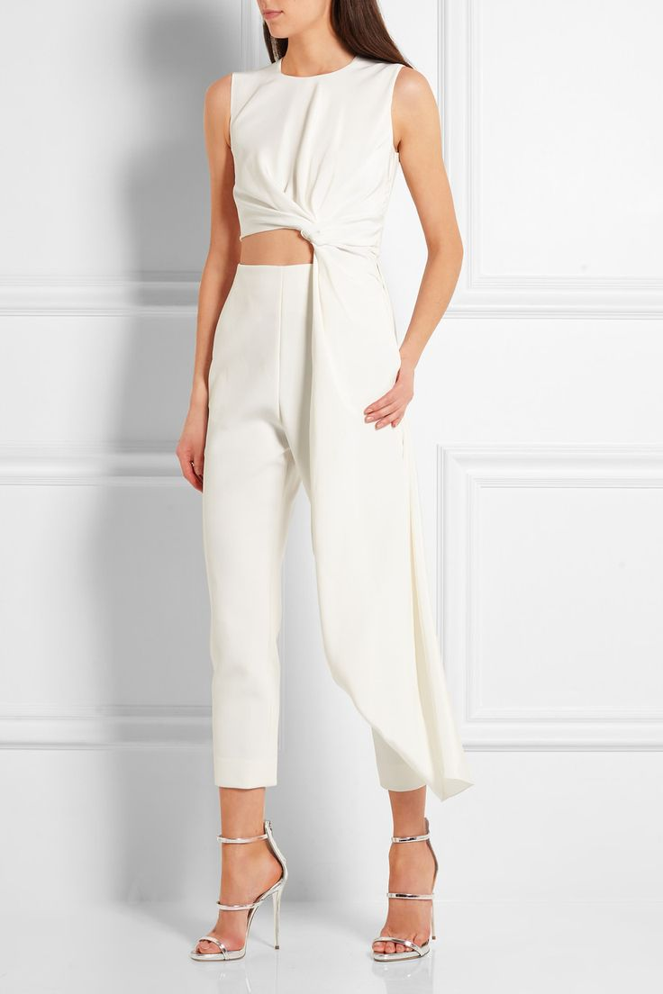 Roksanda's jumpsuit is the perfect alternative to a gown for modern brides. The bodice is crafted from lustrous jersey with a cutout waist and knotted sash that drapes beautifully, creating elegant movement as you walk. The crepe pants are tailored for a flattering slim fit that tapers towards your ankle - complement the cropped length with heels.  Shown here with: Edie Parker Clutch, Giuseppe Zanotti Sandals, Monica Vinader Ring.