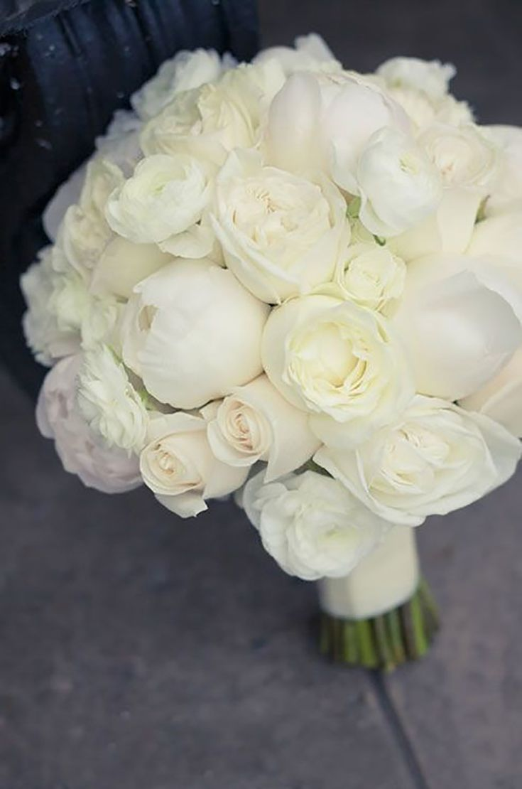 white bridal bouquet features fresh roses peonies and ranunculuses ok to replace peonies with garden roses