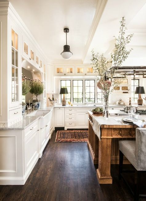Beautiful farmhouse style kitchen with white cabinets and wood island.