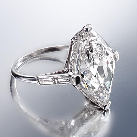 DIAMOND RING, CIRCA 1925. The modified lozenge-shaped diamond weighing 9.18 carats, bordered by 6 baguette and 24 small round diamonds, mounted in platinum