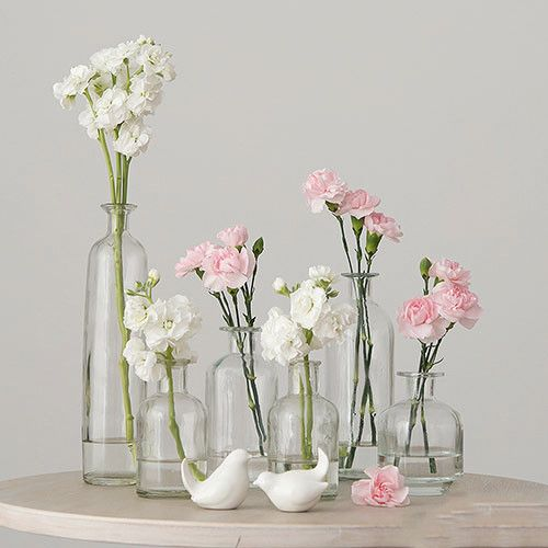 6 Piece Decorative Clear Glass Bottle Set filled with flowers.