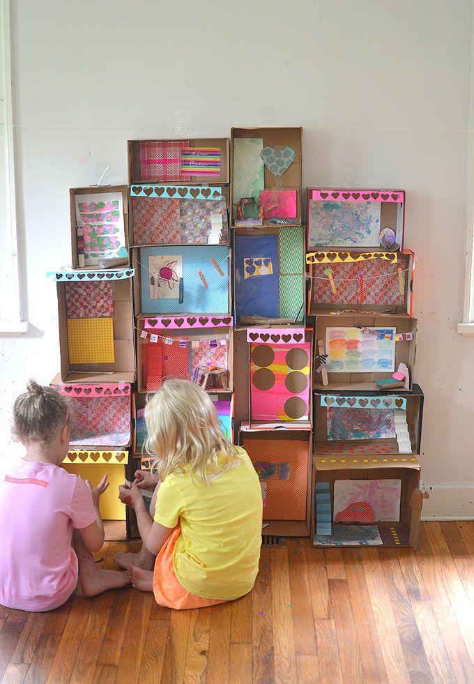 Kinder basteln gemeinsam aus Schuhkartons ein Herrenhaus und dekorieren die Zimmer im