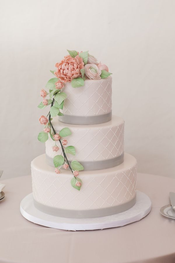 A three-tier wedding cake decorated with a diamond pattern and pink and green sugar flowers. |   Photo by Jaclyn L Photography