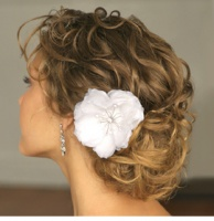 Romantic bride hairdo with light curls and floral hairclip.PNG