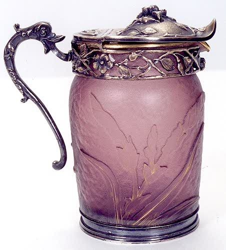 A DAUM CAMEO GLASS SYRUP PITCHER, having an amethyst-purple field with floral motif, gilt highlighted, having Art Nouveau chased and engraved silver gilt metal hinged cover, pouring spout and handle.