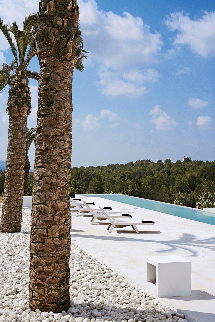 Blanco RADICAL - AD España, © Marco Severini De un blanco impecable y tan intensa como Ibiza, la casa de Alex Estil.les y Xavi Lanau es un contundente volumen geométrico abierto al paisaje lleno de diseño de los 70. En el exterior, grandes palmeras sobre un suelo de cantos rodados. Enmarcando la piscina, el suelo se ha pavimentado combinando el cemento y el polvo de mármol. Las tumbonas de fibra de vidrio son de Habitat.