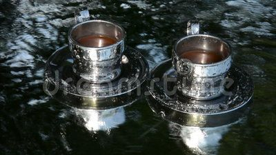 Two coffee cups with the flowing water, indicator of the need to get out of stress in a serene forest-like atmosphere.