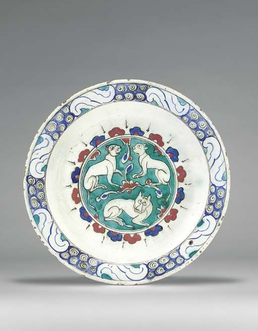 AN IZNIK POTTERY DISH  OTTOMAN TURKEY, CIRCA 1600  With sloping rim on short foot, the white interior with central roundel on green ground, with pair of affronted lions and below, a lion in profile looking out frontally, enclosed in alternating blue and red cusped motifs and radiating black stripes, the cavetto left plain, the rim with alternating wave and scroll in blue, black and green, the exterior with alternating green roundels and blue trefoils,   12¼in. (31.2cm.) diam.