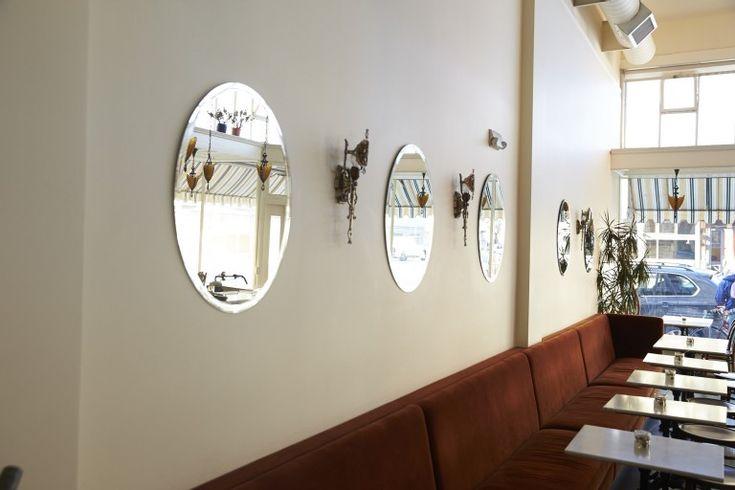Круглые зеркала на стене в интерьере кафе в стиле ретро