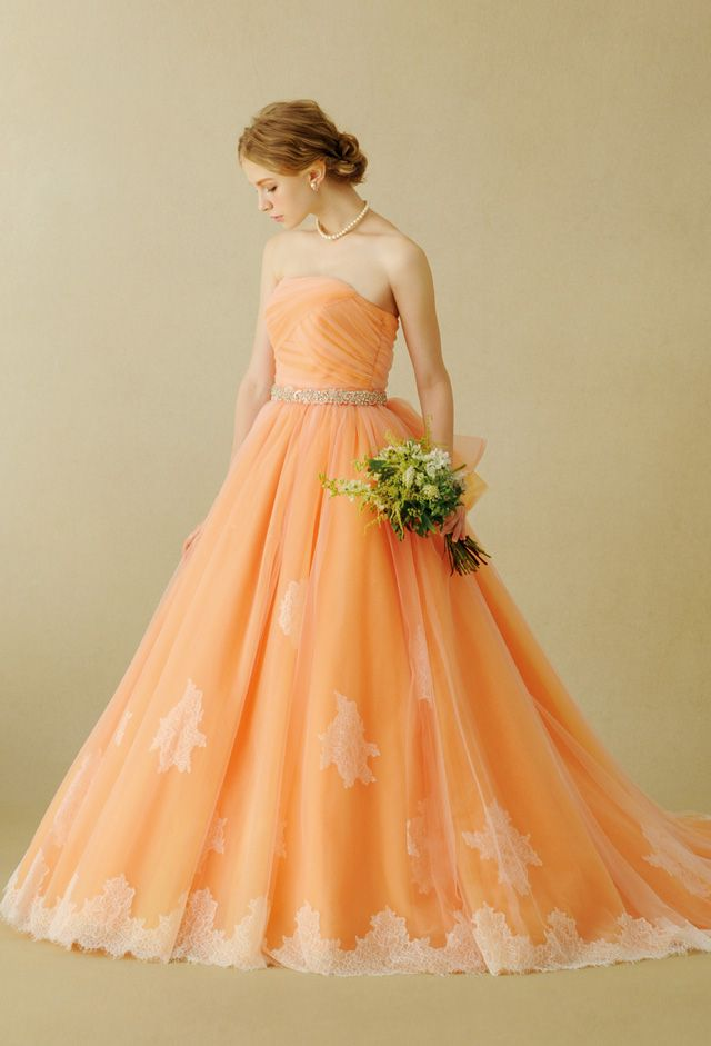 オレンジ、ピンク、ラベンダーの3色が織り成す美しいニュアンスカラーが動きによって様々な表情を魅せるドレス。ビスチェ全体に施したエンブロイダリーレースの上から立体的な花柄のカットレースをランダムにあしらい、チュールスカートと同じ3色のクリスタルを散りばめて華やかに仕上げました。