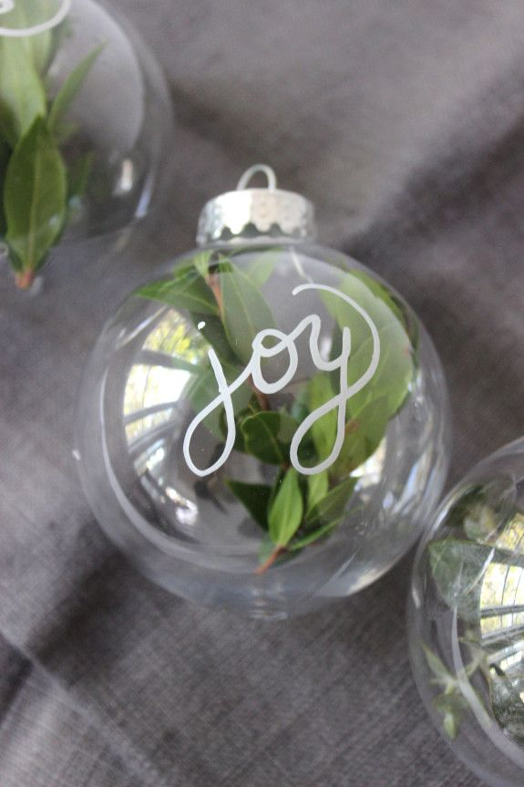 Simple DIY ornaments. Clear plastic or glass ornaments with holiday greenery and pretty writing...a pretty addition to your Christmas tree.