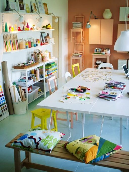This studio has a beautiful big table to work on. I also love all the art materials on the shelves.