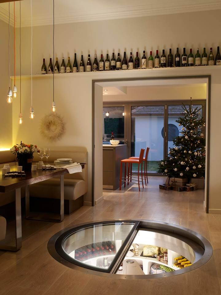 ダイニングの床に埋め込まれた、ガラス扉の螺旋階段状のワインセラー兼食料貯蔵庫