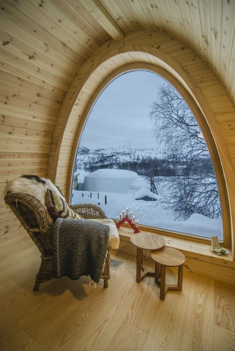Большое полукруглое окно, которое позволяет беспрепятственно любоваться заснеженными пейзажами. Норвегия.