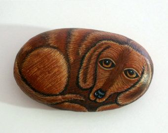 Made to order! A Black tan dachsund dog painted rock with imploring eyes needs adoption to a good home. This sweet Dachshund dog painted rock requires very little to eat, never needs a walk, doesnt bark and wont shed on the couch! Wont you adopt this adorable little puppy dog? He comes with his own soft fleece pet bed to sleep in.  Black and tan, solid black, or solid brown painted rock dachshund dog measures approx. 2 - 3 long x 1-1/2 wide x 1/2 thick and will ship in a padded enve...