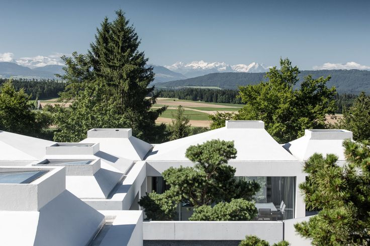 The four courtyard houses are located on a hilly plot on the top of the settlement area of Zumikon/Switzerland. The typology of the courtyard house is a reaction to the strict building regulations of the community, which unable a concentration of the l...
