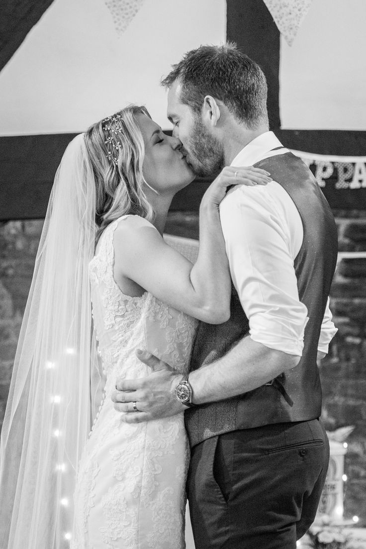 Photo of bride and groom in the Chilham Village Hall, Kent. Wedding kiss. Photo by Mugshot Photography
