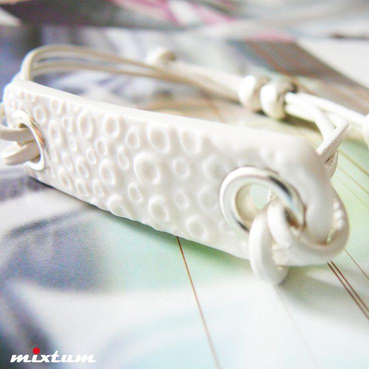 Náramek ... White Justine Náramek tvoří autorský, ručně vyrobený komponent z bílé polymerové hmoty fimo s reliéfem, doplněn stříbrnými kovovými průchodkami ( 5x1,3cm) + bílé kulaté kožené šňůrky. zapínání na posuvné uzlíky - lehce se tedy navléká a zabrání ztrátě.
