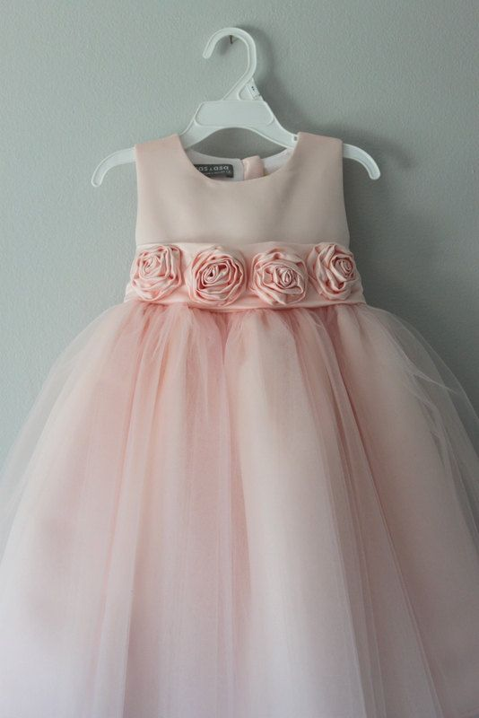 The perfect special occasion dress. A wide sash ties in a generous bow at the back, and a tulle underskirt gives it extra flounce.  Fitted bodice. Sleeveless. Four roses on the front sash. Full skirt. Removable sash. Buttons in back 4 layers of soft tulle (6 layers total on the skirt) Fully lined in 100% cotton for comfort Hand wash or Dry clean.  Handmade in USA  ***Please allow 2 weeks for turnaround time. If you need the dress before 2 weeks, please let us know in the Note to Seller…