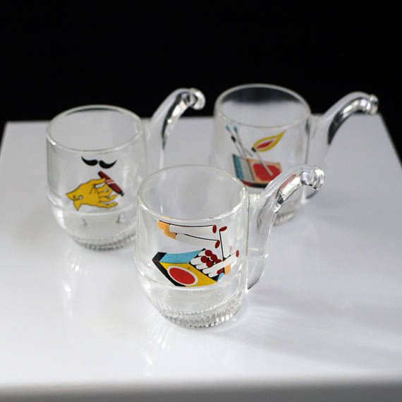 Here is a wonderful trio of cigarette memorabilia. This Set of Three Cigarette Pipe Shaped Shot Glasses are shaped like a pipe adorned with bright pictures of cigarettes, cigar and matches. They are all in excellent condition. They measure approximately 3 x 2 inches. Remember this has been previously owned. See photo for detail and condition. I do my best to describe all items, but if for some reason I have left something out I encourage you to contact me with any questions you may have…
