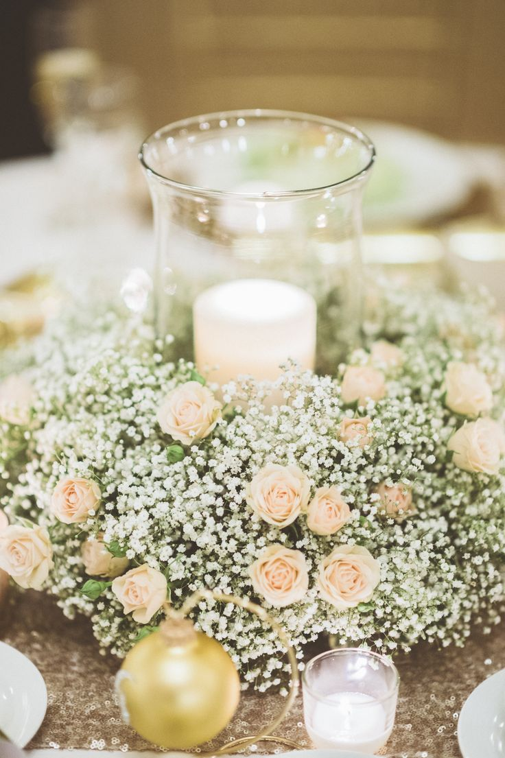 Sweet and charming centerpiece. A hurricane candle surrounded by a wreath of Baby's breath and champagne spray roses. #bellefiorimke #whitewedding #baby'sbreath