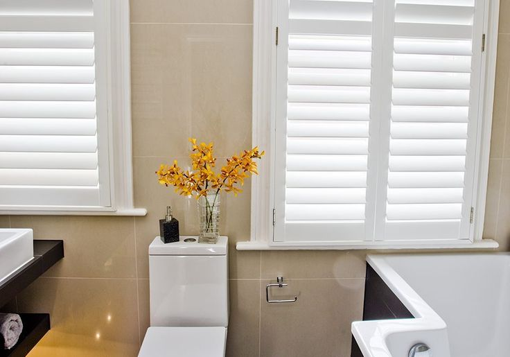 """pushrods are concealed. 3 1/2"""" slats.   Modern looking large louvered shutters in a bathroom."""