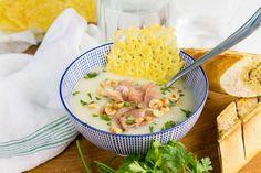 Recept voor bloemkoolsoep voor 4 personen. Met zout, peper, bloemkool, afbakstokbrood, aardappel, kippenbouillon, kookroom, hazelnoot, geraspte kaas, peterselie en ham