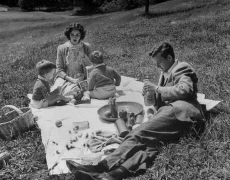 """Jennifer Jones (""""Love Is a Many-Splendored Thing"""") and Robert Walker (Hitchcock's """"Strangers On a Train"""") enjoying a picnic with their sons."""