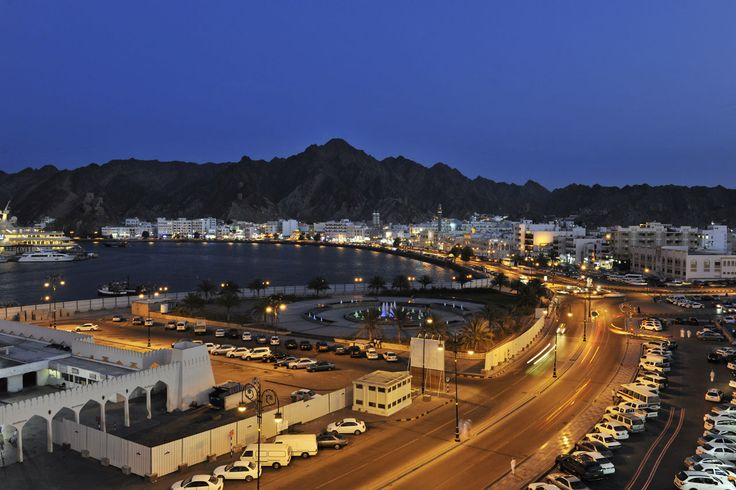 Muscat, the capital city of Oman lies sparkling white, topped with golden minarets in the middle of a maze of brown pleated mountains reaching down to the Arabian Sea.