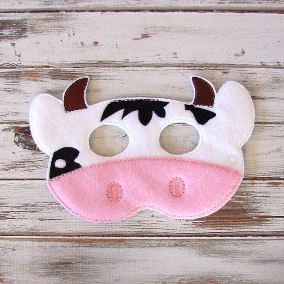 This farm animal cow mask is a great addition to your child's pretend play accessories. Mooooooooove over boring costumes and uncomfortable plastic masks! The Cow Mask is the perfect alternative. Its soft fabric makes it a true pleasure for any kid to wear, and its black, white, brown and pink design is downright adorable. Any kid will be a happy heifer dressing up for a party, school play or Halloween in this creation.  This kids mask is also perfect party favor for the farm animal…