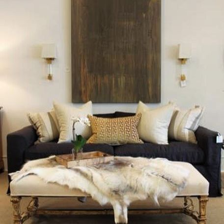Modern and rustic living room decor. Antique Italian bench with reindeer hide, charcoal sofa with gold and brass accents.