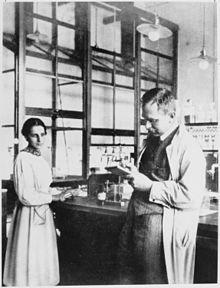 """Lise Meitner und Otto Hahn im Labor, Kaiser-Wilhelm-Institut für Chemie, 1913. Elise Meitner (* 7. November 1878 in Wien; † 27. Oktober 1968 in Cambridge, Vereinigtes Königreich) war eine bedeutende österreichische Kernphysikerin. In einem Brief an einen Freund schreibt sie: """"Sie haben mich nach meiner Einstellung zu Deutschland gefragt. Ich kann sie am besten durch die Worte ausdrücken, ... daß ich mir wie eine Mutter vorkäme, die klar sieht, daß ihr Lieblingskind hoffnungslos mißraten…"""