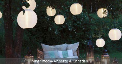 Mit einer Gartenbeleuchtung mit Lampions und Laternen lassen sich warme Sommernächte ganz romantisch gestalten. Durcheinander gewürfelte Möbel, wie die Holzbank, die Teekiste und der Couchtisch aus dem Wohnzimmer, geben dem Ganzen einen romantischen Flair.