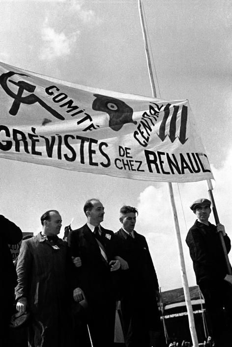 Montrouge near Paris. At the Buffalo Bicycle Track. Celebrating the Front Populaire victory. Renault factory strikers carrying banner combining symbols of the Communist, Radical and Socialist Parties. The Radical symbol is the Phrygian cap. The Socialist symbol is the 3 arrows. June 12th, 1936.