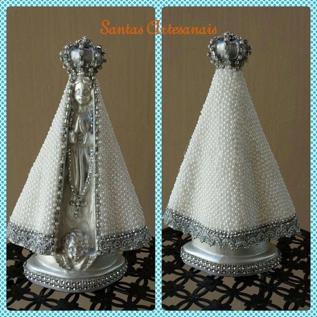 Nossa Senhora Aparecida, na cor prata, perolada, em gesso e manto revestido manualmente em pérolas e detalhes strass, com 26 cm de altura.