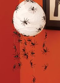 Glue spiders on fishing line and put over a lantern or lampshade for a creepy element.