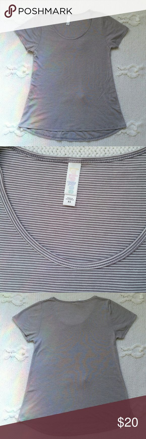 "{LuLaRoe} pinstripe classic tee, sz XS Classic tee of a great neutral color that will go well with many outfits. Off-white and light purple pinstripe (some may see the purple as grey). Poly-rayon blend, very soft and non-sheer fabric. Worn and washed once, absolutely excellent condition, like new! No pilling, no stains or holes.  Size XS but will fit S loosely. Check with the measurements before purchase: bust is 17"" across flat lay, length is 25"" on front and 26.5"" on the back.  Price is…"