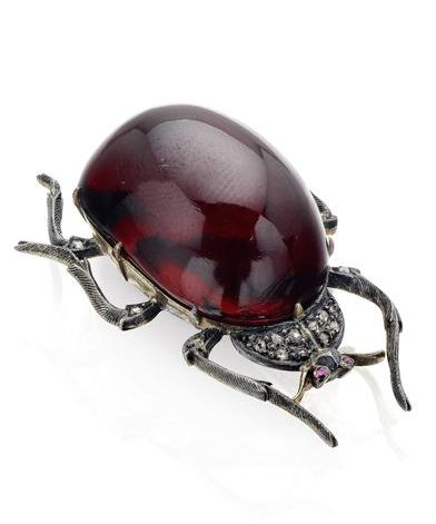 A 19th century garnet beetle brooch The body of the beetle set with an oval cabochon-cut garnet carbuncle, the head set with rose-cut diamonds, mounted in silver on gold, length 42mm