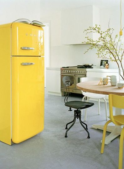 Yellow in the kitchen. A dash of yellow can enliven any space. Love the retro Smeg refrigerator. Photo via at-hermans