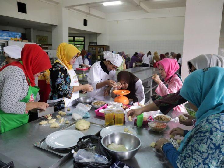 Peserta pelatihan menimbang berat adonan kue