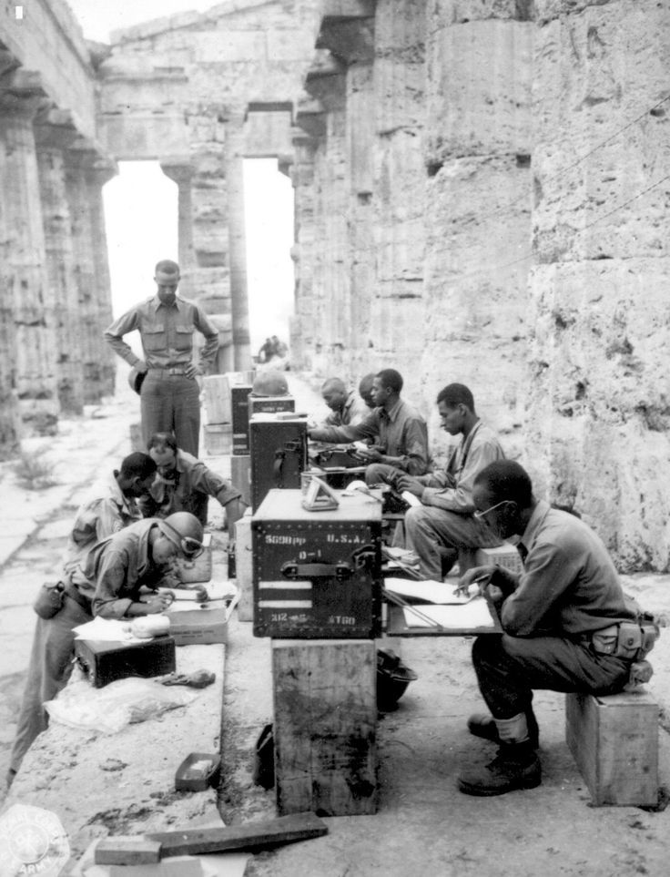 A company of African American soldiers of the US Army working at a makeshift office located at an ancient Neptune temple in Italy, 22 Sep 1943.