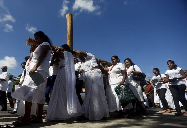 Catholic devotees hold a wooden cross during a Good Friday mass at a church in Colombo, Sr...