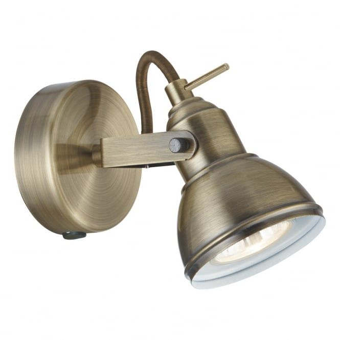 An industrial style single wall spotlight in an antique brass finish, perfect for lighting in industrial themed settings and in living rooms and bedrooms. The rocker switch on the base allows it to be switched individually which is ideal for bedside lighting.