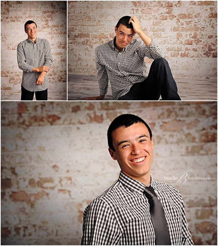 Senior pictures of Skyline High School boy laughing in check shirt by brick wall at Studio B Portraits